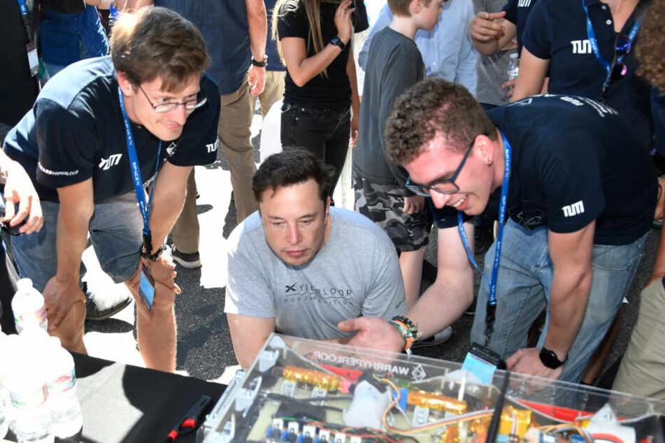 Münchner Studenten der TU München zeigen Elon Musk (M), Vorstandsvorsitzender von Space Exploration Technologies Corp. (SpaceX), bei einem Hyperloop-Wettbewerb ihre Kapsel.