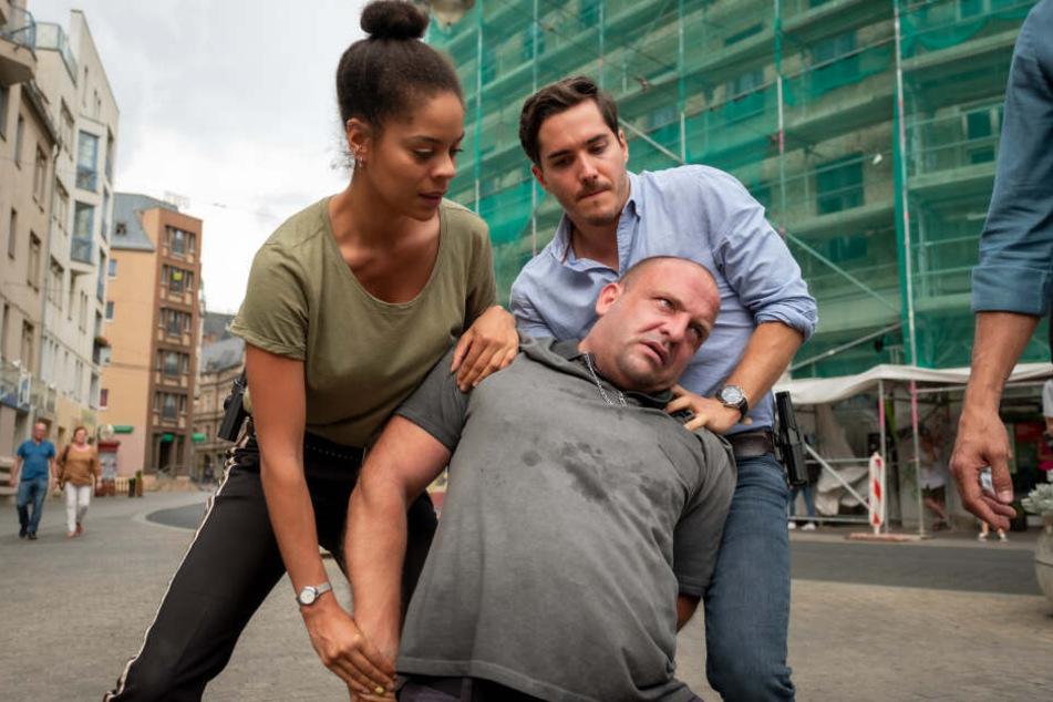"""Ann-Christin """"AC"""" (gespielt von Jane Chirwa) und Kilian (Francois Goeske, r.) nehmen den Ex-Boxer Marcel John (Urs Rechn) auf Halles Straßen fest."""