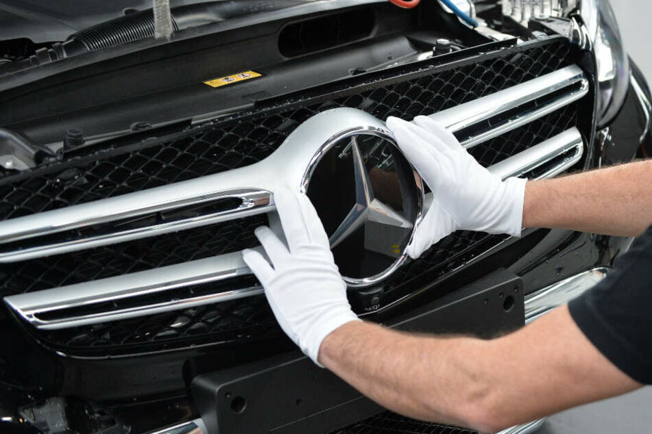 Ein Mitarbeiter befestigt den Mercedes-Stern an einer C-KLasse.