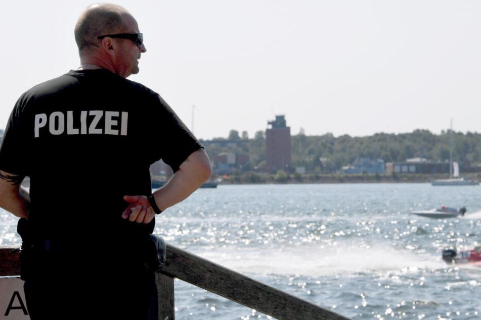 Ein Polizist steht bei der Kieler Woche an der Förde.