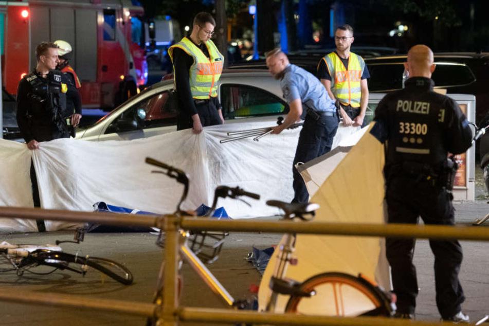 Polizeibeamte schirmen die tödlich verletzte Frau mit Decken ab.