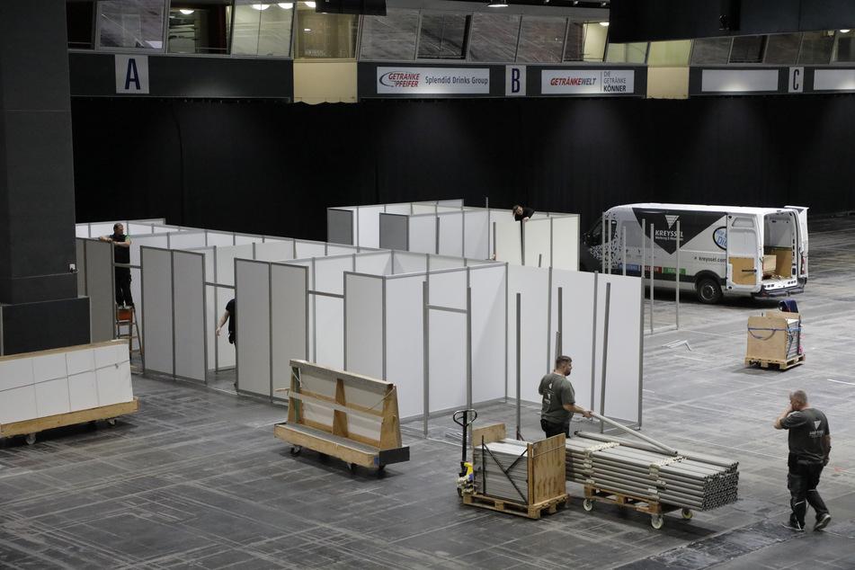 In der Chemnitzer Messe entsteht ein Corona-Erstaufnahmezentrum: Mitarbeiter der Messe errichten erste Behandlungskabinen.