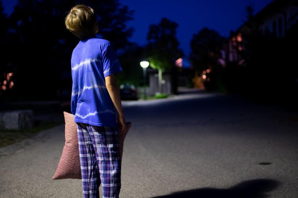Ein Junge im Schlafanzug steht nachts mit einem Kissen in der Hand auf einer Straße. (Symbolbild)