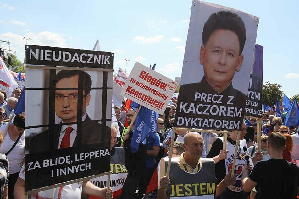 """""""Nieder mit dem Diktator Kaczynski"""" (re.) und dem """"Verlierer"""" Ziobro (li.) steht auf Plakaten beim Protestmarsch """"Wir sind und bleiben in Europa"""" in Warschau."""