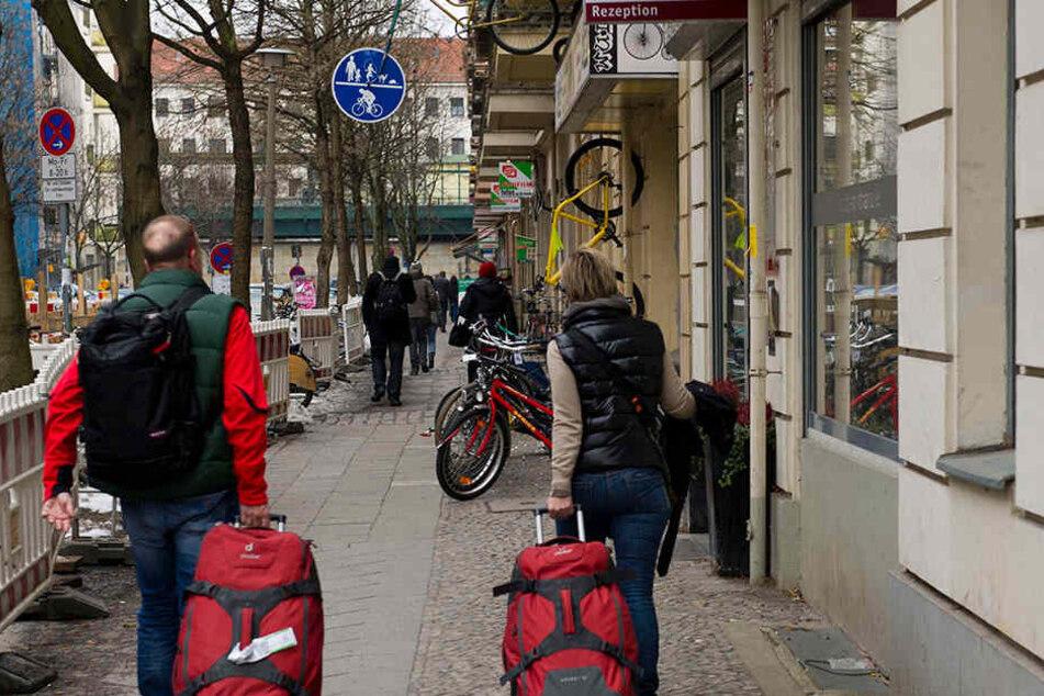 Urlauber mit Gepäck gehen im Prenzlauer Berg an einem Wohnhaus vorbei, in dem Ferienwohnungen vermietet werden.