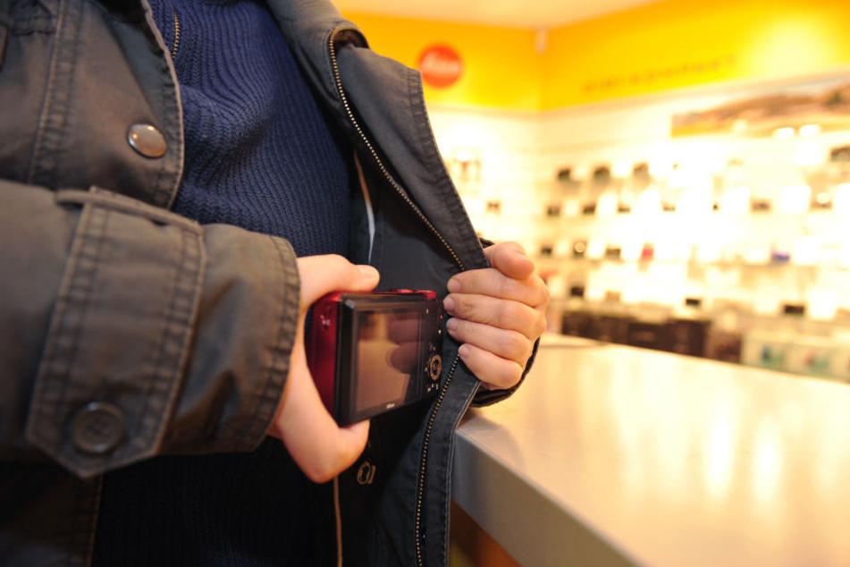 Eine Frau steckt in einem Fotogeschäft in Stuttgart eine Kamera unter ihre Jacke. (Symbolbild)