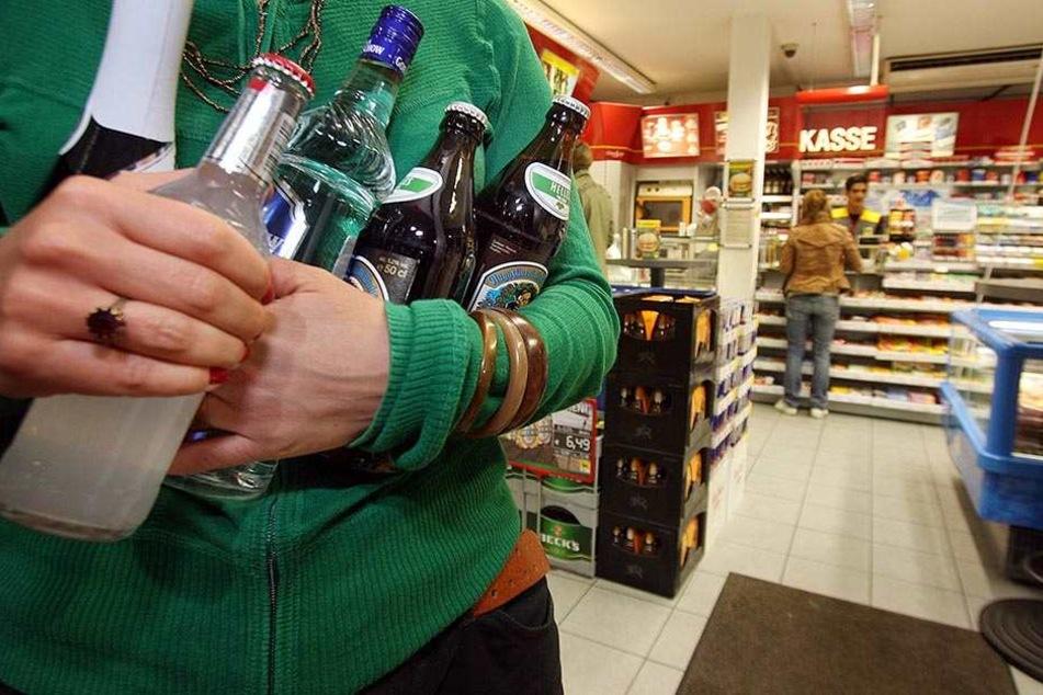 Eine junge Frau schleppt Bier und Schnaps aus einer Tankstelle. Die Aktion Jugendschutz wünscht sich mehr Kontrollen (Symbolbild).