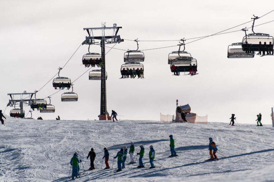 Unter einem Skilift fahren Menschen Ski. (Symbolbild)