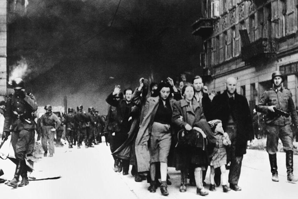 Warschau, Mai 1943: Mit erhobenen Händen werden jüdische Frauen, Männer und Kinder von deutschen SS-Soldaten aus dem brennenden Ghetto der polnischen Hauptstadt getrieben.