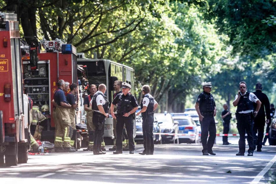 Einsatzkräfte stehen vor dem Bus, in dem ein Fahrgast Mitreisende mit einem Messer attackiert hatte. (Archivbild.)