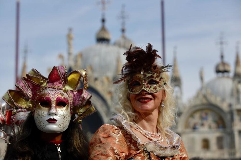 Zwei kostümierte Frauen in Venedig mit den landestypischen Masken.