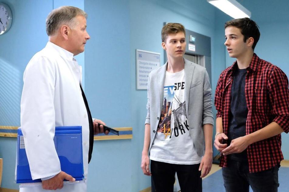 Bastian (M., der Sohn von Sachsenklinik-Verwaltungschefin Sarah Marquardt) und Jonas (r., Dr. Heilmanns Enkel) wollen vom Klinikleiter wissen, wie schnell ihr Sänger Jimmy wieder auf der Bühne stehen und ob der Auftritt stattfinden kann.