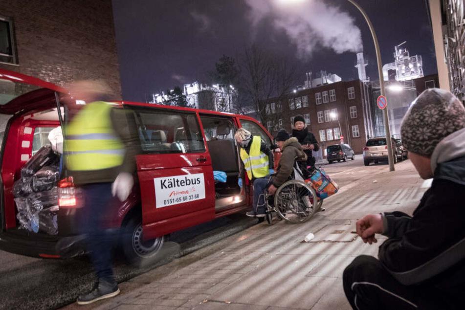 Die freiwilligen Helfer helfen Menschen mit Rollstuhl, die auf der Straße leben, in den Kältebus.