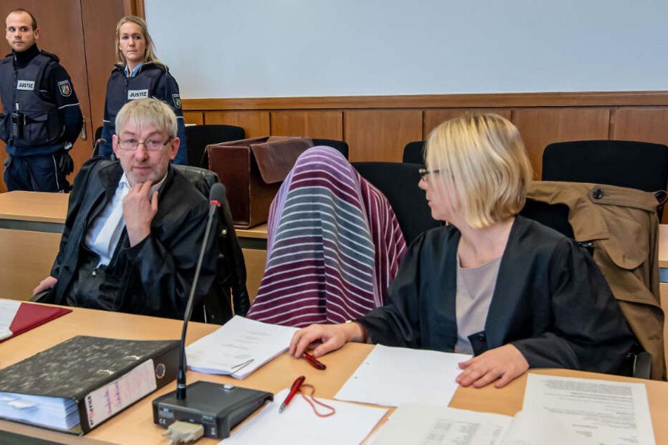 Die Angeklagte sitzt zu Beginn des Prozesses zwischen ihren Anwälten Andreas Trode (l) und Julia Kusztelak.