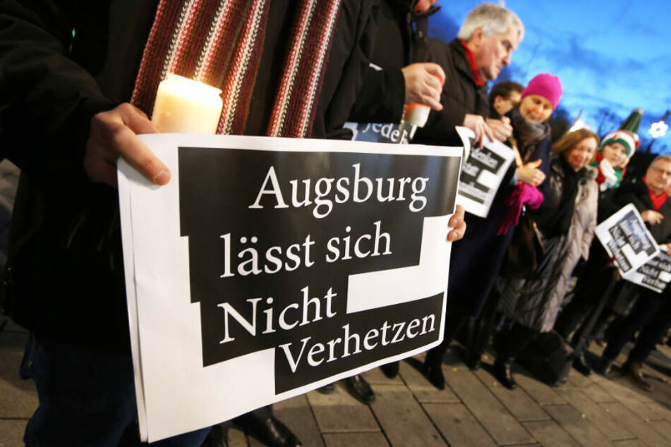 Menschen demonstrieren in Augsburg gegen politische Instrumentalisierung.