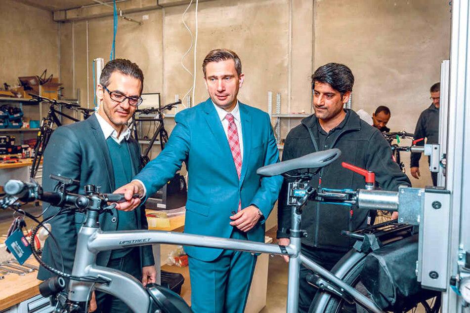 """Flüchtling Aminzadeh Khosro (36, r.) wird zum Monteur geschult. Wirtschaftsminister Martin Dulig (44, SPD) lobte """"Fahrrad XXL Emporon""""-Geschäftsführer Hamidreza Ameli (46, l.) für sein innovatives Job-Projekt."""