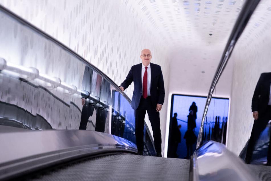 Peter Tschentscher fährt die Rolltreppe in der Elbphilharmonie hinauf.