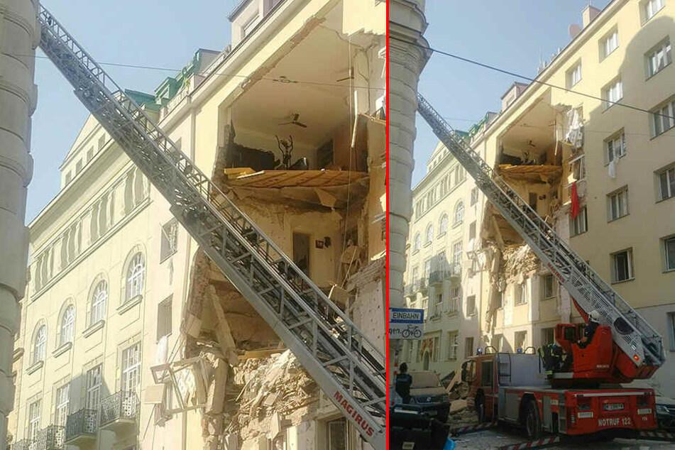 Ein Feuerwehrauto steht mit ausgefahrener Leiter vor einem teilweise eingestürzten Mehrfamilienhaus.