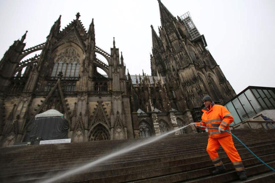 Ein Mitarbeiter der Stadt reinigt die Freitreppe am Kölner Dom (Archivbild).