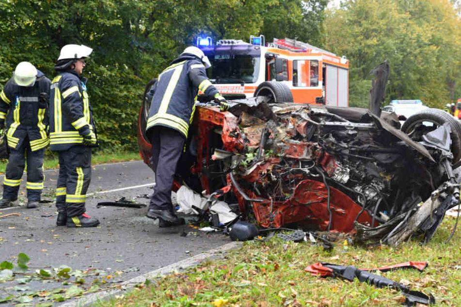 Einsatzkräfte bei den Überresten des Unfallwagens.