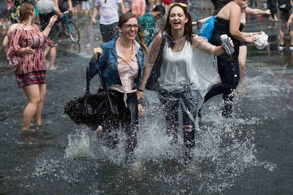 """Die Teilnehmer ziehen in Berlin während eines Regenschauers beim Christopher Street Day (CSD) unter dem Motto """"Mehr von uns - jede Stimme gegen rechts"""" für die Rechte von schwulen, lesbischen, bi- und transsexuellen Menschen über die Straße des 17. Juni z"""