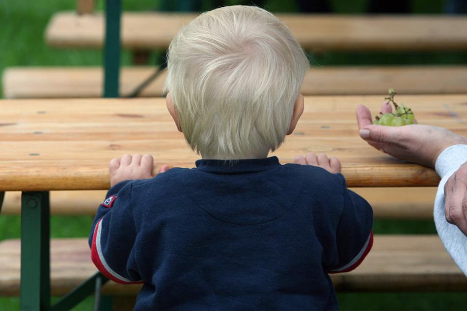 Ein kleiner Junge sitzt beim Sommerfest der Kinderhilfsorganisation Arche auf einer Bank.