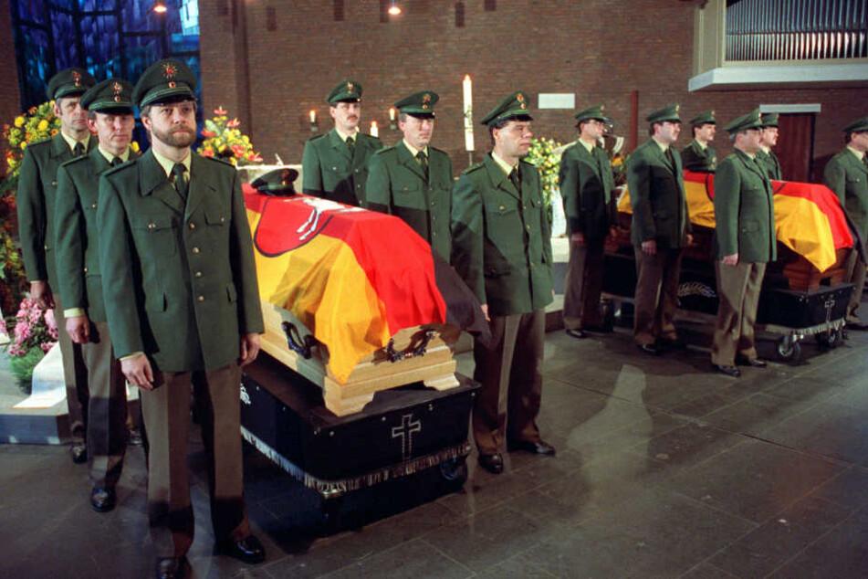Beamte der Polizeiwache Holzminden halten Totenwache an den mit Flaggen bedeckten Särgen bei einem Trauergottesdienst in Holzminden (Niedersachsen).