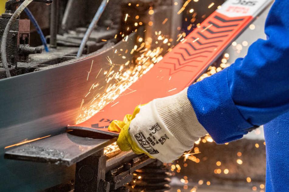 Ein Mann bearbeitet einen Ski in der Produktion des Skiherstellers Völkl in Straubing.