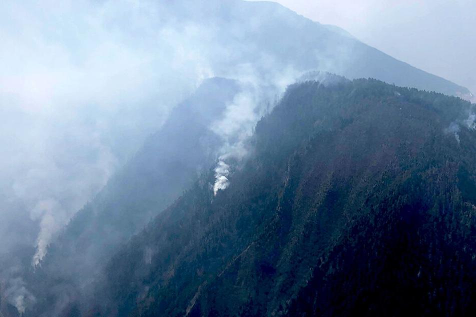 Rauch steigt von einem Waldgebiet an einem Hang im Kreis Muli in der südwestchinesischen Provinz Sichuan auf.