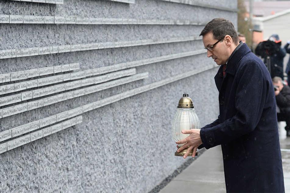 Mateusz Morawiecki, Ministerpräsident von Polen, stellt eine Kerze an ein Denkmal, das an Polen erinnert, die während des Holocaust Juden gerettet haben.