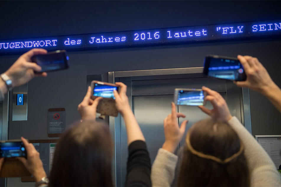 """Die Worte """"Fly sein"""" flimmern in München als """"Jugendwortdes Jahres"""" über den digitalen Newsticker eines Hotels."""