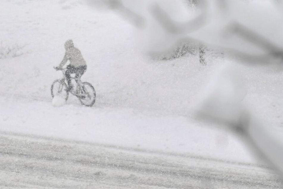 Eine Radfahrerin fährt über eine verschneite Straße in Salzburg.