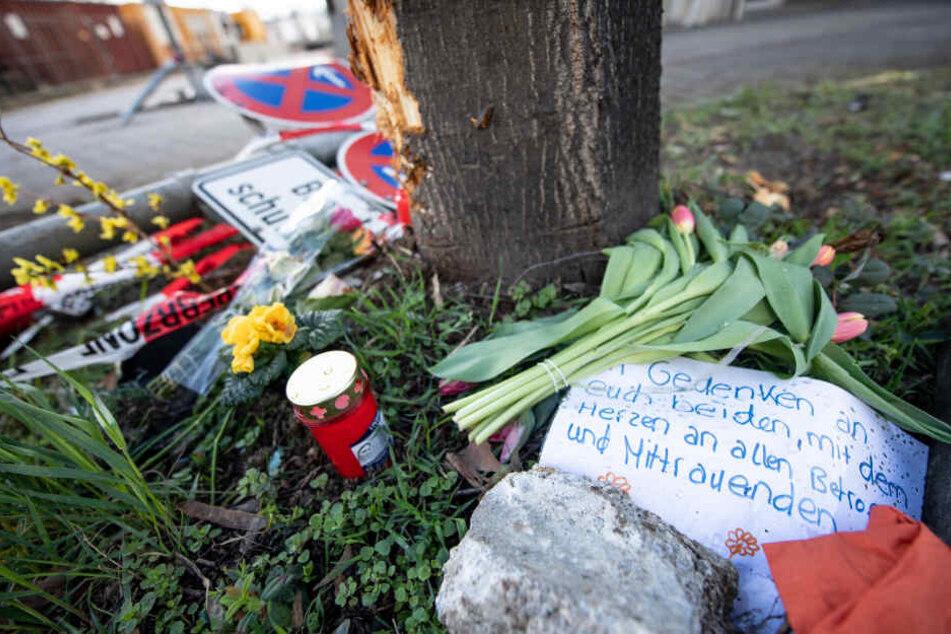 Verbogene Verkehrssschilder und eine Trauernachricht liegen an der Unfallstelle in der Rosensteinstraße in Stuttgart.