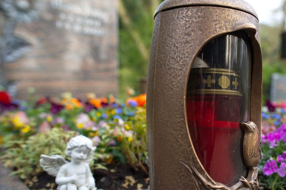 Vandalen haben Figuren und Kuscheltiere von einem Friedhofsgrab entwendet.