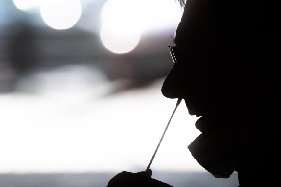 In einem Schnelltestzentrum wird ein Nasen-Abstrich bei einer Person genommen.