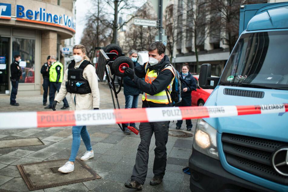 Polizeibeamte sichern Spuren am Tatort. Rechts ist im Anschnitt der überfallene Geldtransporter zu sehen. Gegen einen der mutmaßlichen Räuber beginnt am Donnerstag vor dem Kriminalgericht in Berlin-Moabit der Prozess.