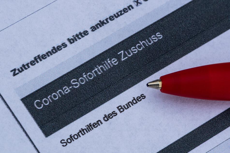 Ein Stift liegt auf einem Antrag für den Corona-Soforthilfe-Zuschuss.