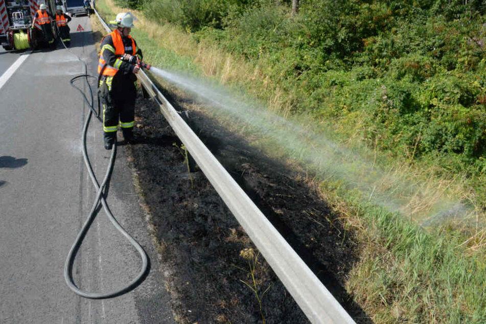 Ein Feuerwehrmann löscht das in Brand geratene Gras