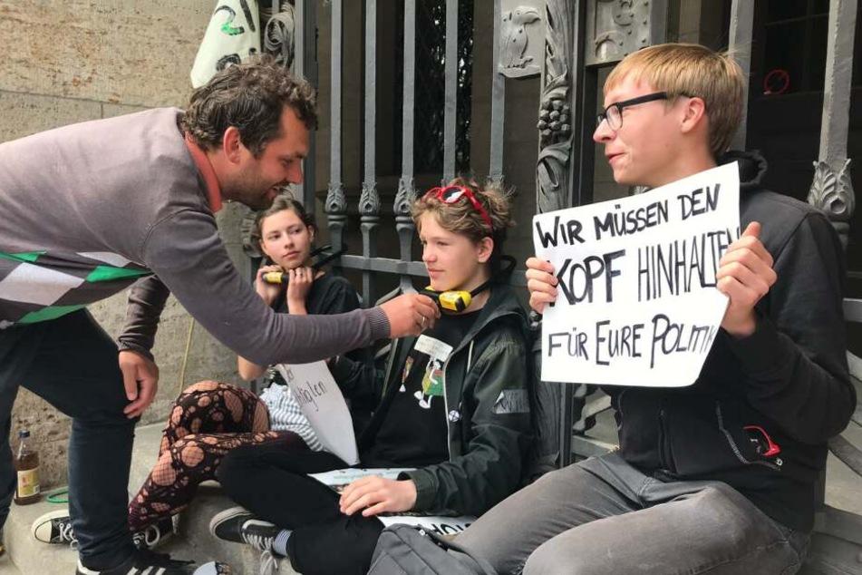 Stadtrat Christopher Zenker von der SPD befreit einen Aktivisten mit dem passenden Schlüssel.