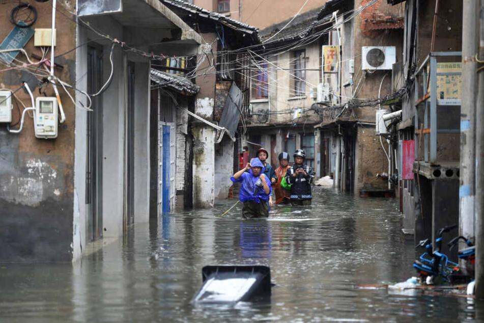 Menschen gehen zwischen Häusern auf einer von Wasser überfluteten Straße. Mit heftigem Regen und Sturmböen hat Taifun Lekima das chinesische Festland erreicht.