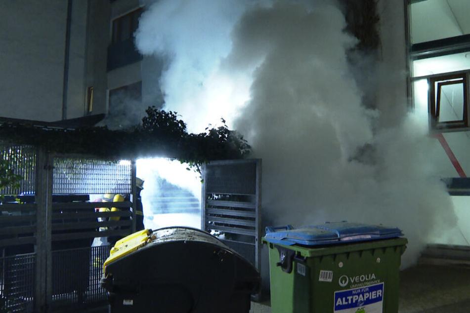 Die Einsatzkräfte löschen die brennenden Müllcontainer.