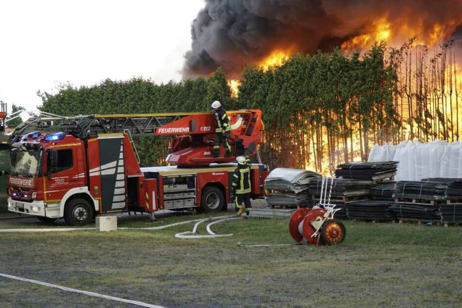 Feuerwehrleute stehen mit ihrem Fahrzeug neben einem Brand auf dem Gelände eines Kunststoffverarbeitenden Betriebs.