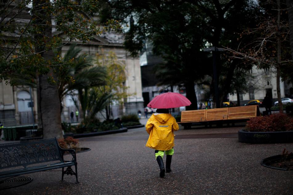 Santiago: Ein Mensch mit Regenschirm geht durch die fast leere Innenstadt inmitten der Corona-Pandemie.