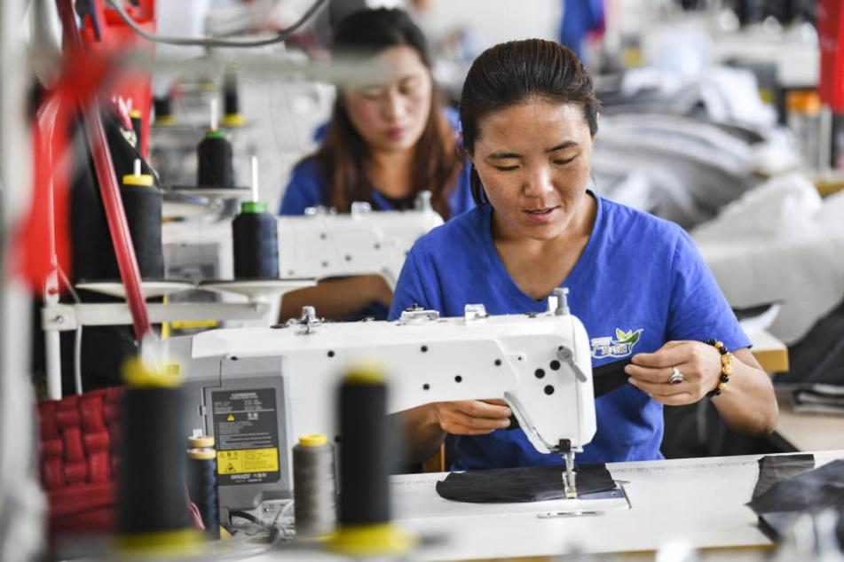 Arbeiterinnen stellen Kleidung in einem Bekleidungsunternehmen in China her.