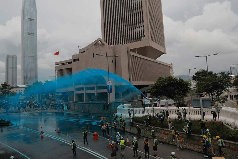 Die Polizei geht mit Wasserwerfern gegen Demonstranten vor und besprüht sie mit blauer Farbe.