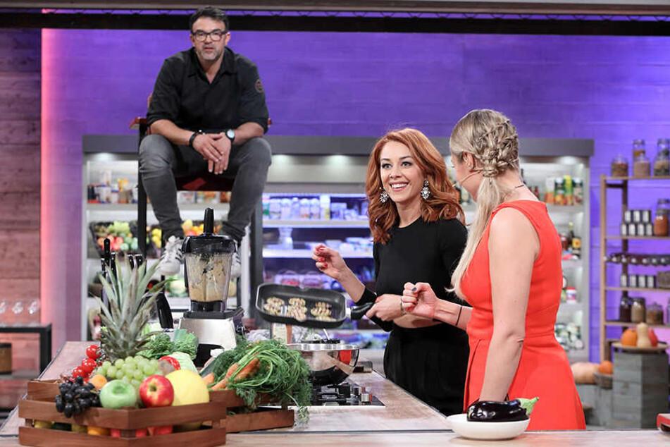 Beim Kochen bekommt Oana (Mitte) seelische Unterstützung von Profi-Koch und Coach Tarik Rose (links) und Moderatorin Ruth Moschner (rechts).