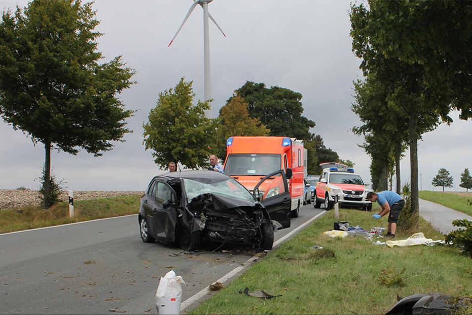 Mitten auf der Fahrbahn steht der demolierte Toyota. Drumherum liegen Unfalltrümmer.