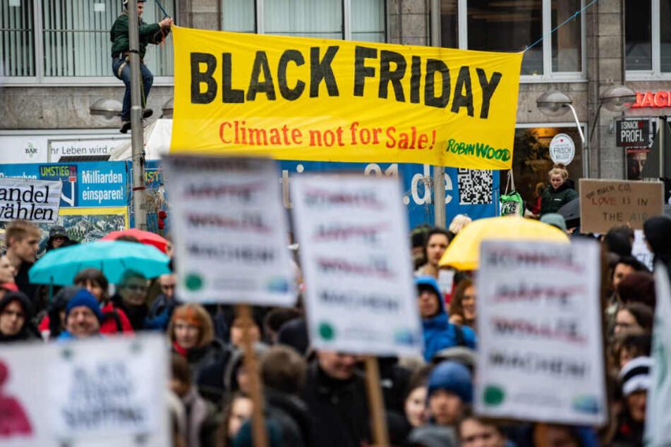 """Demonstranten von Fridays for Future hängen am Freitag in Stuttgart ein Plakat mit der Aufschrift """"Black Friday, Climate not for Sale!"""" auf."""