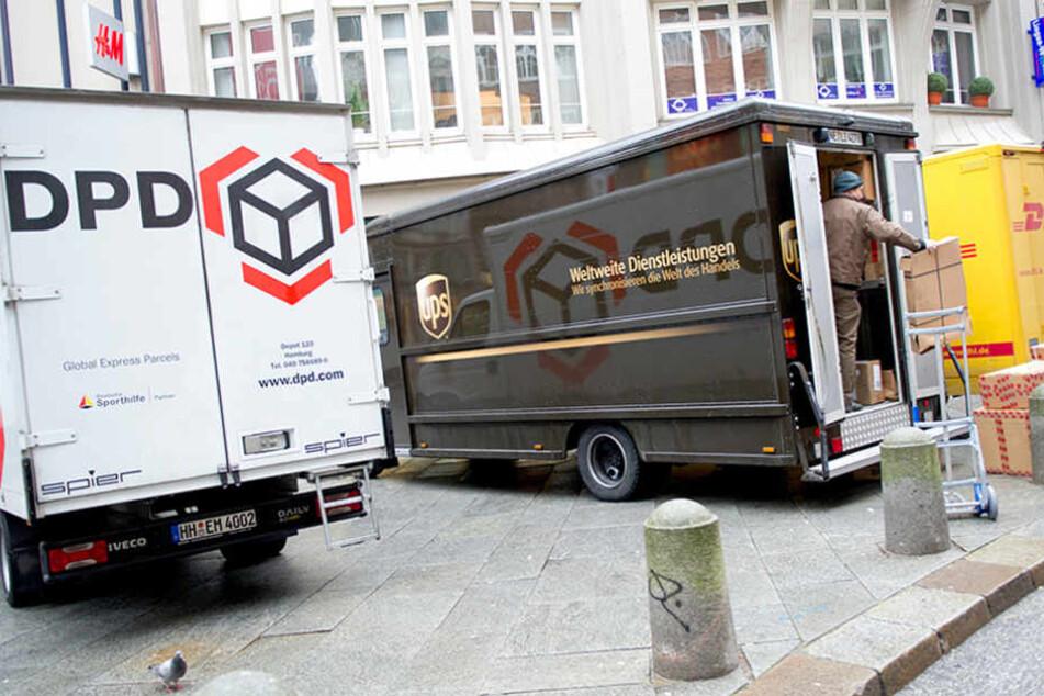 Transportwagen der Logistikunternehmen DPD, UPS (United Parcel Service) und DHL stehen in der Innenstadt von Hamburg.