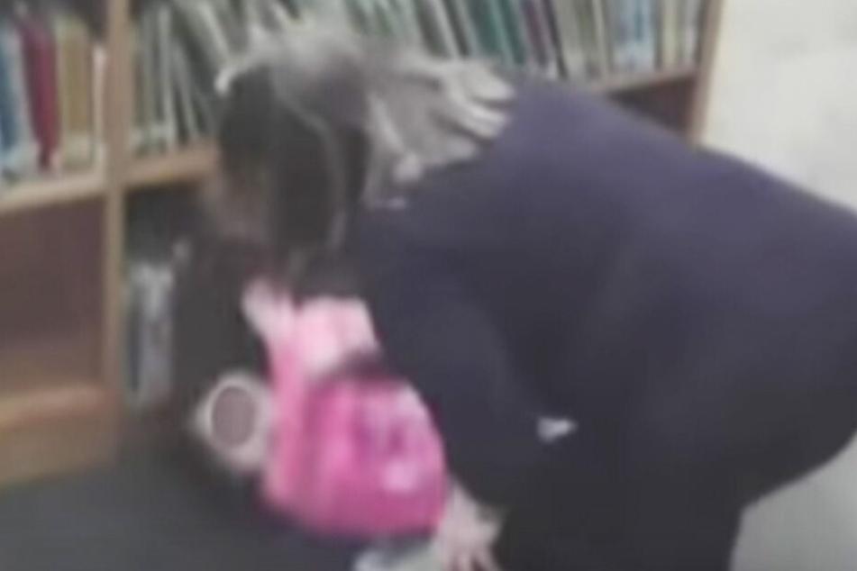 Auf den Videoaufnahmen ist zu sehen, wie die Lehrerin das Mädchen aus dem Bücherregal zerrt.